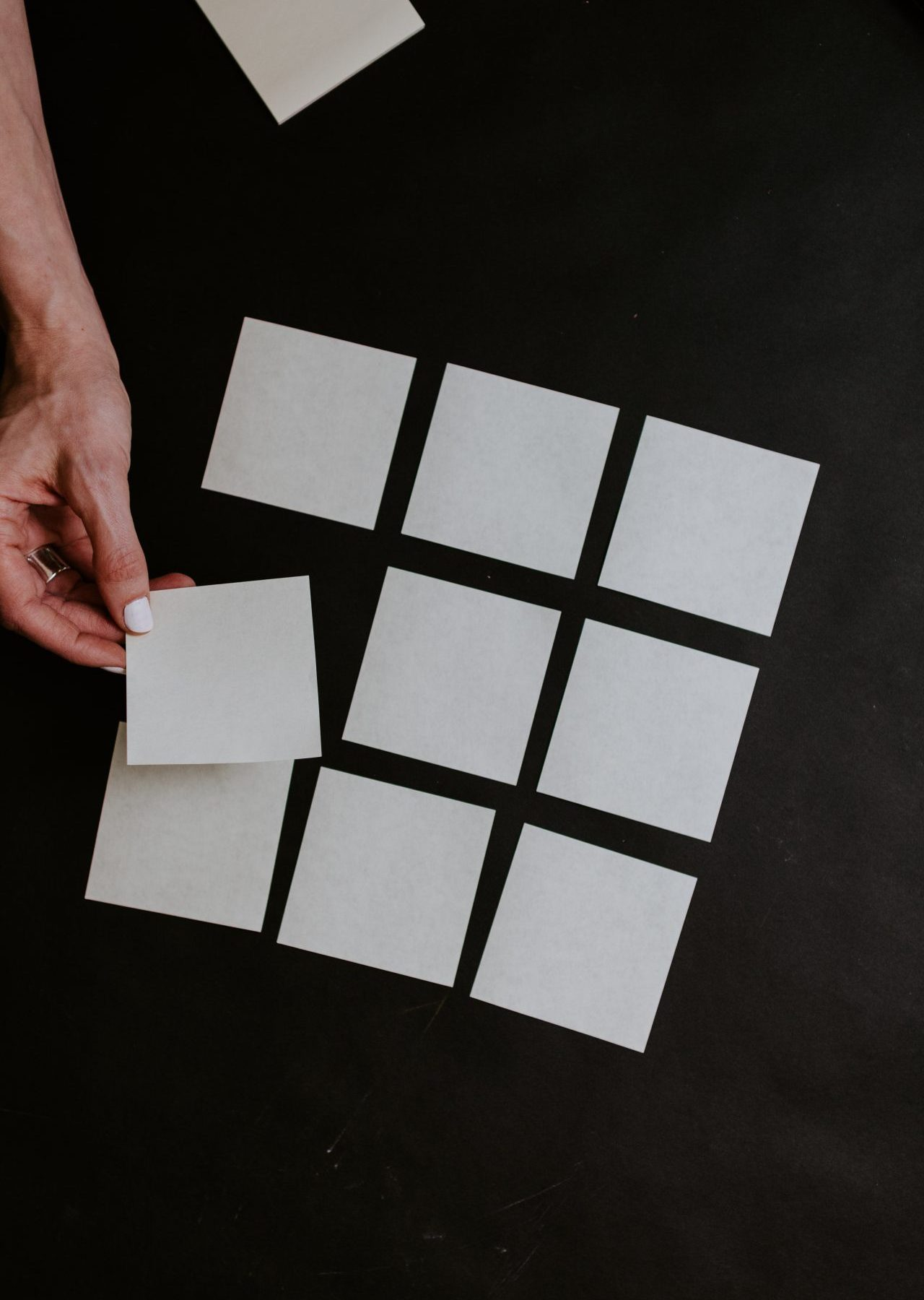 person holding white and black checkered card